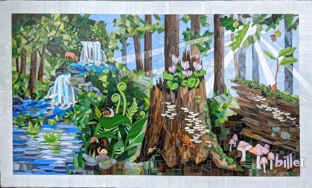 The glass mosaic shows a forest scene with a center tree and a log fallen near it and plenty of flora and fauna, a waterfall, a deer, snails and mushrooms in the background.