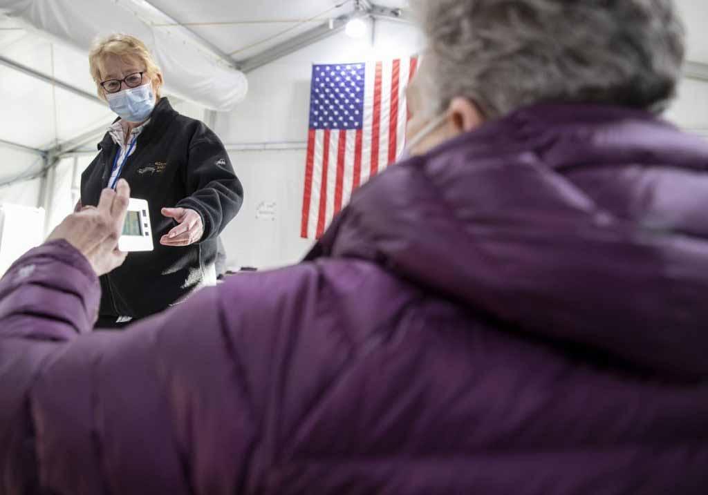 Una mujer con una máscara se pone de pie y busca un temporizador digital de una mujer sentada. Detrás de ellos, una bandera americana cuelga en la pared.