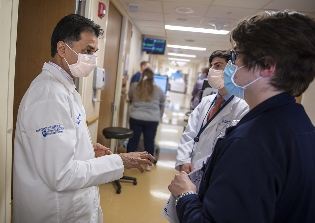 Dr. Sanjay Yadav, left, a psychiatrist at Hershey Medical Center, stands in a hallway at the hospital, gestures and talks to College of Medicine resident Joseph Malone, center, and third-year student Blaine Prichard. Yadav is wearing a white coat with the Hershey Medical Center logo on the sleeve and a face mask. Malone is wearing a white coat with the College of Medicine logo on it, a shirt and tie and face mask. Prichard is wearing a blazer and face mask.