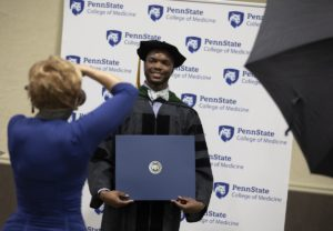 A man smiles for a photo as he holds his diploma.