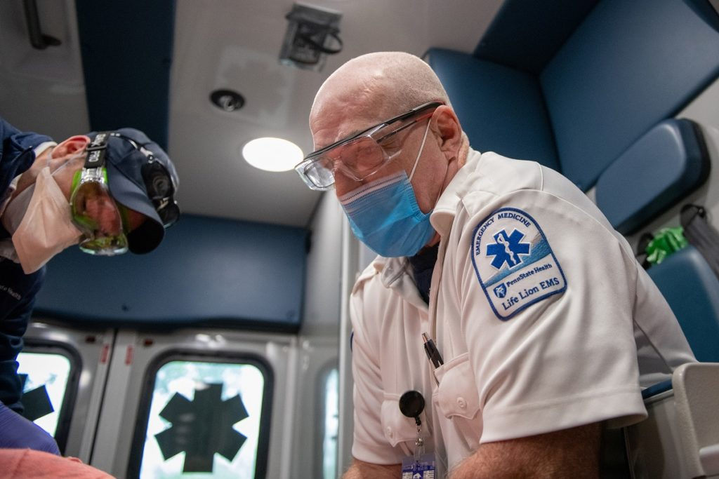 """Paramedic Doug Young, who is bald and wears glasses and a face mask, leans over a patient, who isn't seen, in an ambulance. Young wears a short-sleeve shirt with a patch on the sleeve that says """"Penn State Health Life Lion EMS."""" Samuel Walter, an EMT wearing a ball cap, goggles and face mask, is also leaning over the patient."""