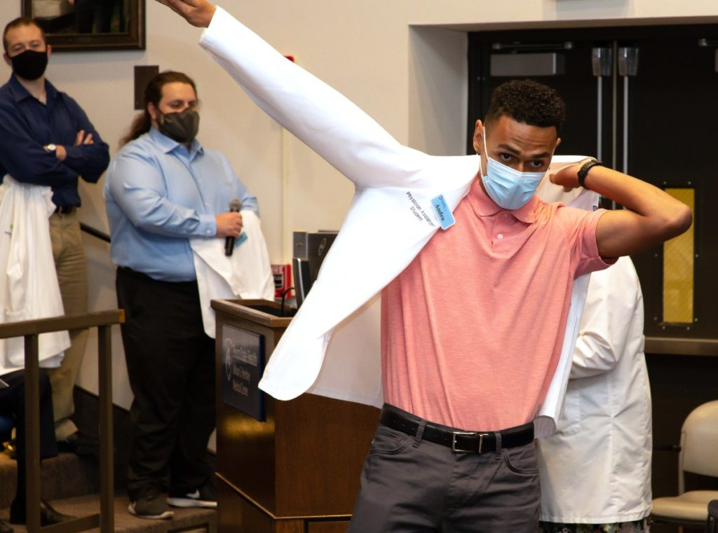 Andru Smith, incoming physician assistant student, puts on his white coat during a ceremony.