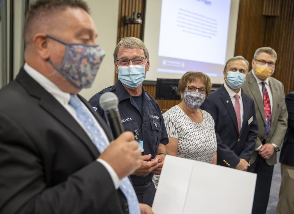 Rex Carmichael, who wears glasses, a mask and his EMS uniform, looks over at Steve Lyle, who wears a suit and tie and a mask and is speaking into a microphone. Two other men and a woman flank Carmichael to his left. The group stands at the front of an auditorium with a large screen in the background.
