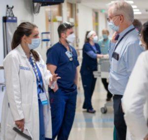 Una mujer con matorrales y una máscara facial habla con un hombre con una máscara facial y una camisa deportiva y corbata de moño en el pasillo de un hospital.