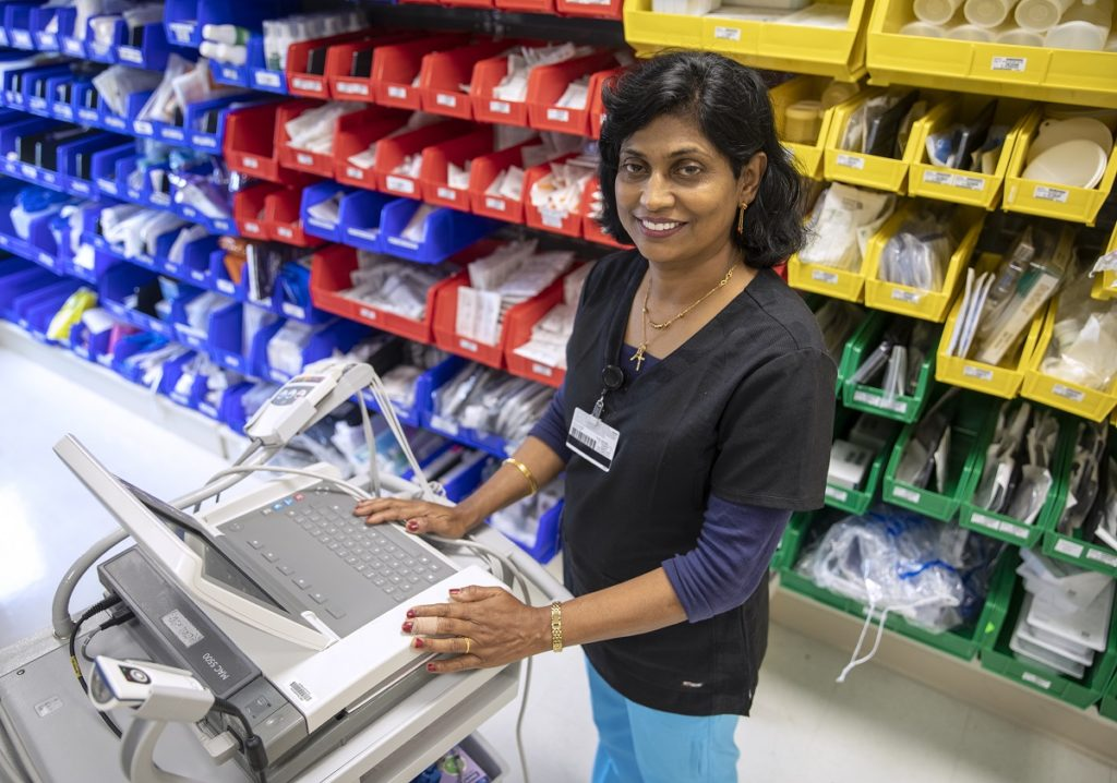 Sherly George stands with her hands on a medical computer. She has shoulder-length hair and is looking at the camera and smiling. She is wearing a long-sleeved top with a smock over it, a necklace with a cross and a nametag on her top. Behind her are bins with medical supplies.