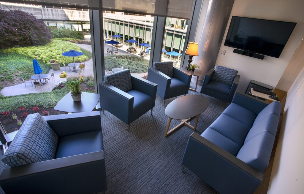 A room in the CARE Center includes a couch, four chairs, two tables, and a TV on the wall. It overlooks a courtyard with tables and umbrellas.