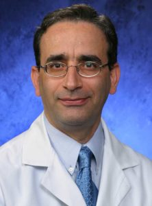 Dr. Nasr Ghahramani, wearing a white coat, poses for a professional headshot.