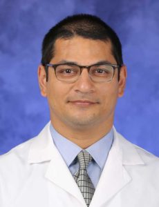 Dr. Moses Mathur, wearing a white coat, poses for a professional headshot.