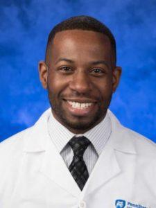 Dr. Ify Ndukwu, wearing a white coat, poses for a professional headshot.