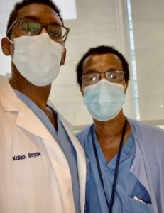 Tadesse Bogale, right, and his son, Kaleb, look at the camera as they pose for a selfie. Both are wearing face masks and glasses. Tadesse is wearing scrubs and a lanyard around his neck. His taller son is wearing a white coat with his name on the left.