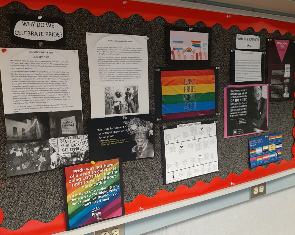 A large bulletin board features a number of facts about LGBTQ+ Pride Month, including why it is celebrated, a timeline, quotes, and photos.
