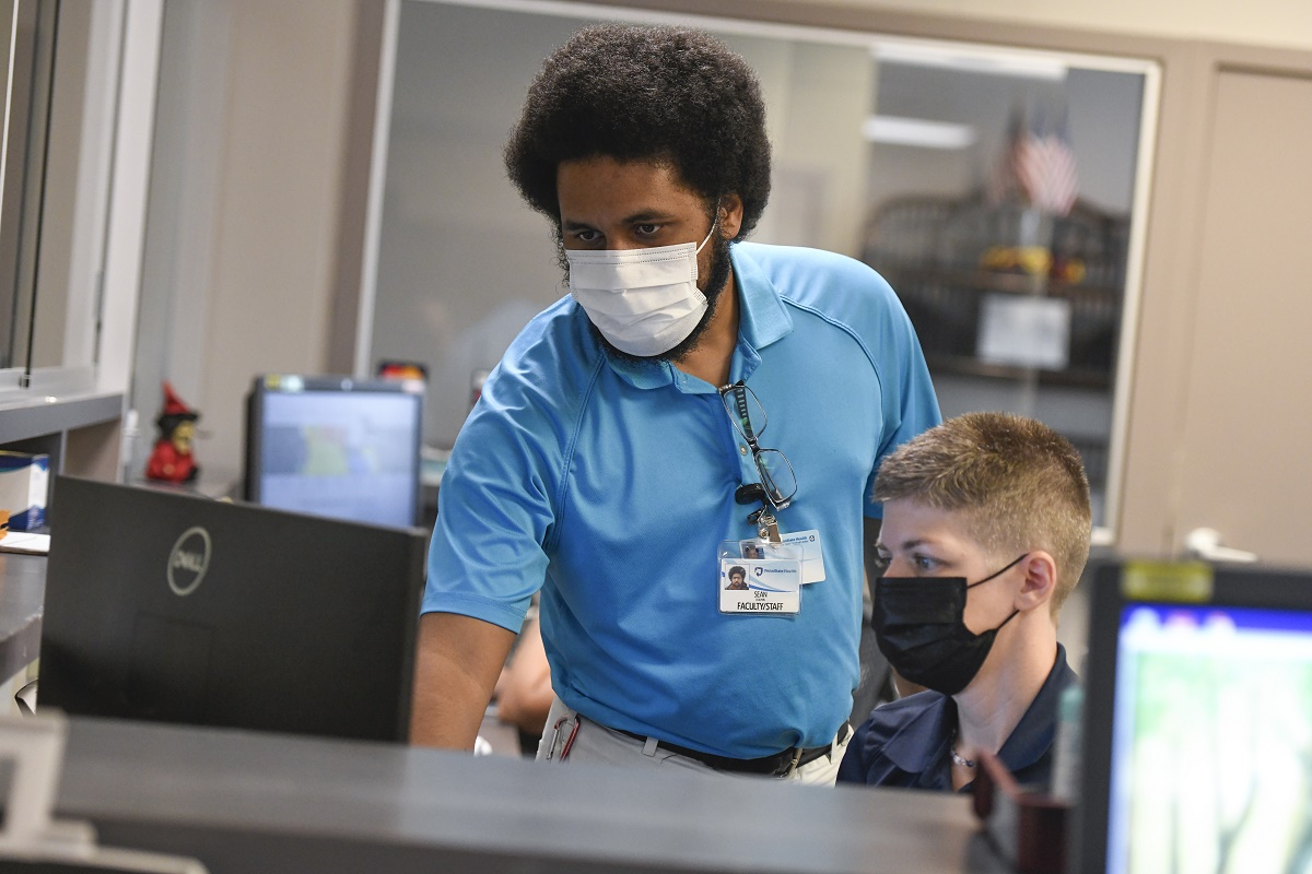Penn State Health Information Services senior support specialist Sean Dolphin leans over a woman and looks intently at a laptop. Both are wearing face masks. He has curly hair and a beard and is wearing glasses, a polo shirt and a nametag. She has short hair and is wearing a polo shirt. A laptop screen is in the foreground on the right.