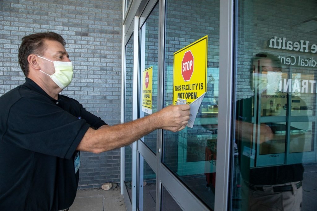 A man with a face mask is peeling a sign off a door.