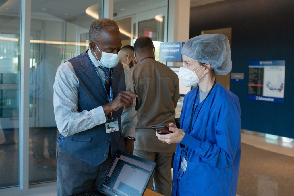 A man with a mask is in a hospital hallway talking to a nurse with a mask and hair covering.