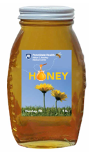A glass jar of honey bears a label that reads Penn State Health Honey and has pictures of flowers and bees.